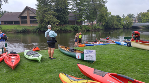Kayak and canoe owners inspect their watercraft before entering the water.
