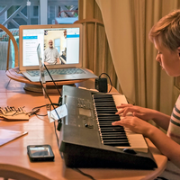 Girl playing the piano with laptop open in next to her