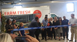 The ribbon cutting image has numerous staff and organizational partners of the Flint Fresh Food Hub.