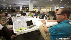 Bill Lennertz presenting to a group of stakeholders seated at a table during a charrette.