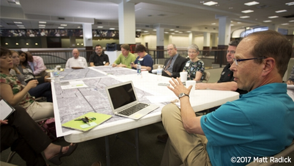 Image of Bill Lennertz presenting to a group of stakeholders seated at a table during a charrette.