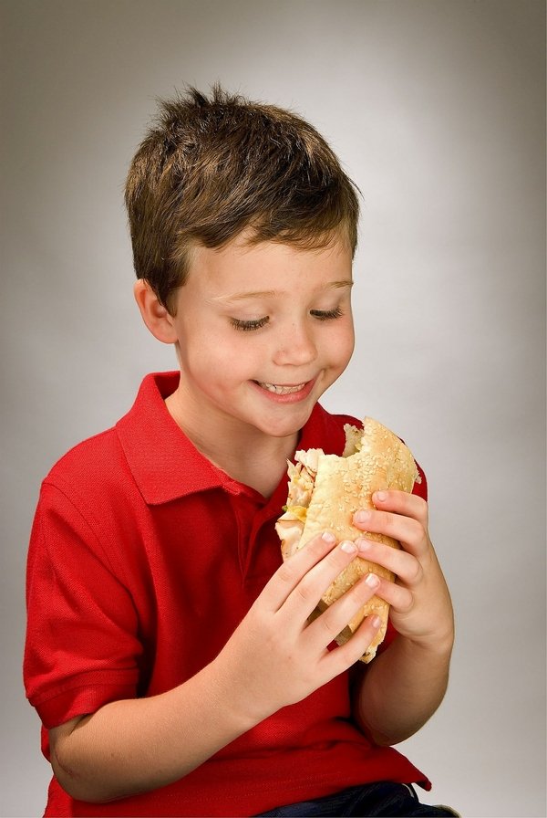 Child in red polo eating sandwich