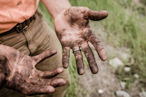 A man's hands covered in dirt and filth.