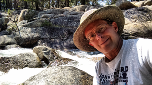 Photo of Robert Chipman in front of nature and rocks.