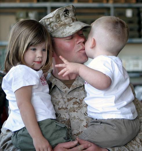 Military dad holding kids