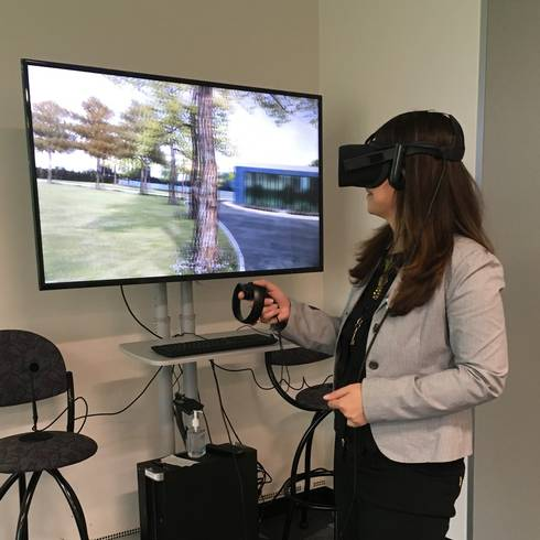 A woman wearing virtual reality head gear demonstrates use of this equipment with hand-held controls with a monitor in front of her showing her changing perspectives on the screen.