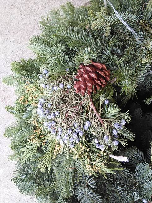 Fresh evergreen wreath using juniper (blue berries) and white cedar (green immature cones) for accents. This wreath is for sale at Bloomer's Flowers and Gifts, Roscommon. Credit: Julie Crick