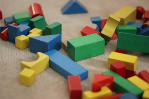 Help your child create a new play scheme by combining toys, for example add trucks and rocks to set of blocks. Photo credit: Pixabay.