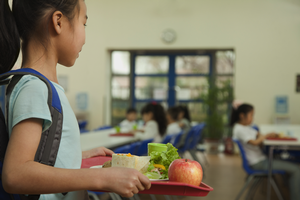 Young girl carries tray of food in cafeteria