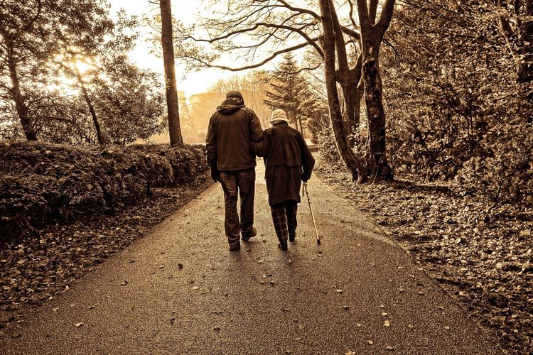 Two adults walking down a nature path, one holding a cane.