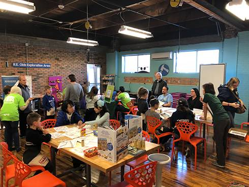 Children, parents, and students interacting and the Design & Build Day.