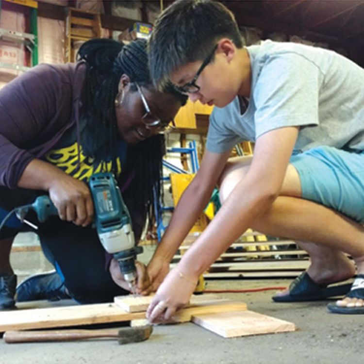 Two students constructing window shutters.