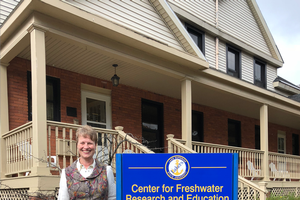 Beth Christiansen stands near a sign at Lake Superior State University that reads Center for Freshwater Research and Education. As Education and Outreach Specialist she will work with the general public, students, and educators across the state to learn of the importance of the Great Lakes waters and each individual's unique role in protecting and preserving the larger system through their actions at the local level.