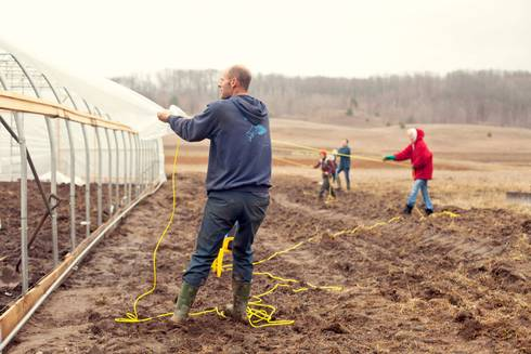 Aaron Brower (front) works with the family to build Bluestem Farm's new hoophouse.