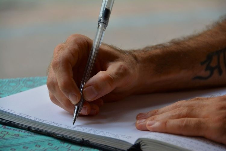 A close-up image of someone's hands as they write in a notebook with a pen.
