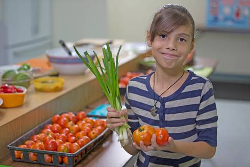 Young girl holding vegetables