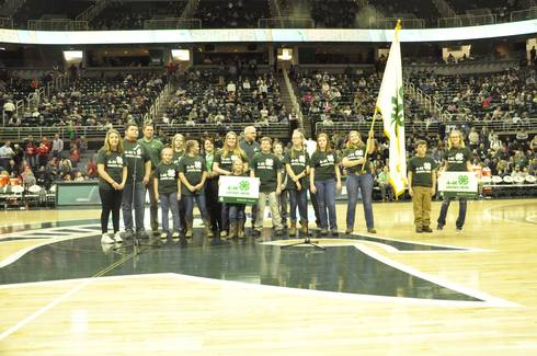 Group of Michigan 4-H'ers wearing 4-H apparel standing in the center of the Spartan's Breslin Center.