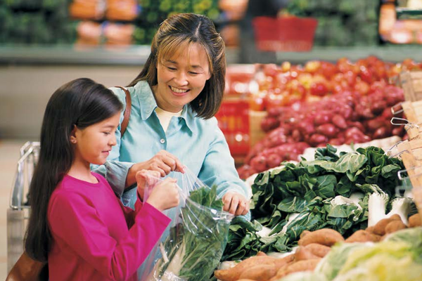 A woman and her daughter shop for fresh produce.
