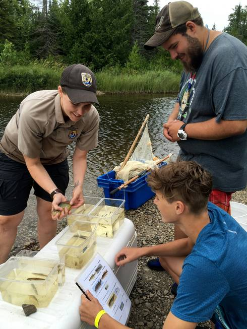 U.S. Fish & Wildlife staff helping youth ID fish