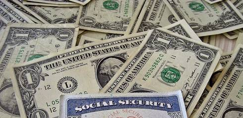 a pile of money and the edges of a social security card