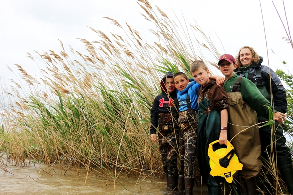 MSU Extension educator Tracy D'Augustino with fifth graders from Au-Gres-Sims standing in front of the phragmites on Charity Island.
