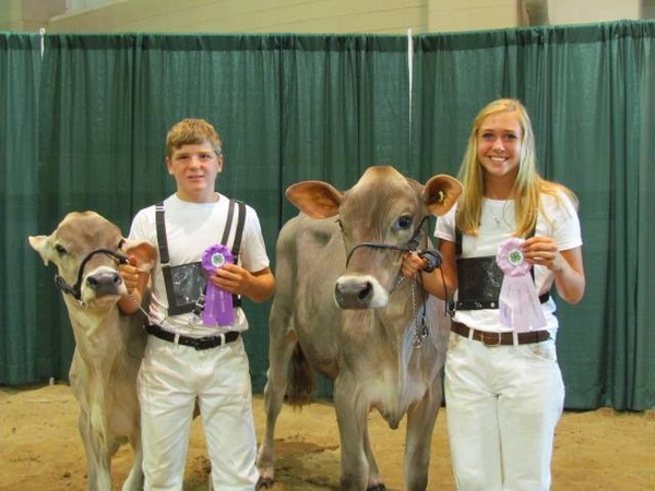 Stoney Buell (left) and Kristen Burkhardt (right) stand with their champion heifers after the Brown Swiss show during the 2016 Michigan 4-H Youth Dairy Days. Photo: Sara Long.