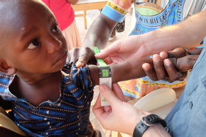 A child having their arm measured during a clinical trial in Malawi.