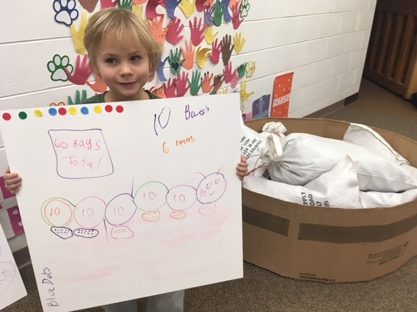 An Alcona County first grader shows the math they did to calculate the soil they would need to plant a raised pollinator garden