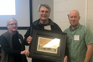 Dennis Fulbright (middle) receiving the Chestnut Pioneer Award from Roger Blackwell (left), president of Chestnut Growers Inc., Josh Springer (right), and Midwest Nut Producers Council president.