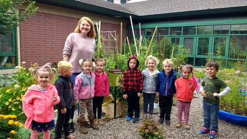 Elizabeth Slajus, advanced Extension Master Gardener, with children at the Woodland Childcare School Garden in Kingsford, Michigan. Photo by Sharon Quick-Dulan, Woodland Childcare Center director.