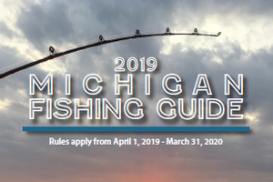 The cover of the Michigan Department of Natural Resources fishing guide for 2019 shows a sunset over a lake with the sun's reflection in the water.
