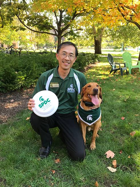 Photo of Ming-Han Li, director of the School of Planning, Design and Construction with Zeke the Wonderdog.
