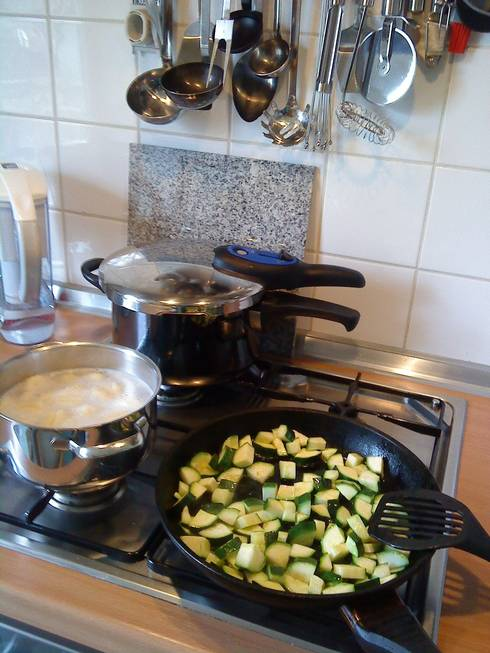 Stove with pressure cooker, zucchini, and boiling corn in pot.