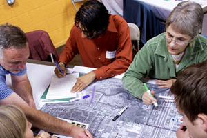 A group of men and women work together on a project during a charrette.
