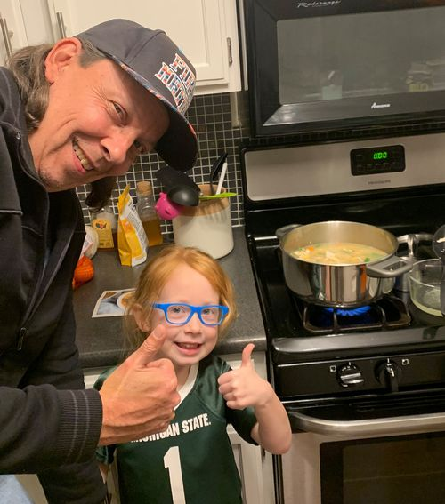 Man and girl give thumbs up next to soup pot on stove
