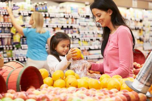 A child and her mother choosing healthy snack options at the grocery store.