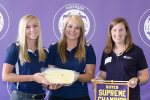 Michigan Dairy Ambassadors Kristen Burkhardt (left) and Charlie McAlvey (center) celebrate with Jolene Griffin (right), United Dairy Industry of Michigan, as the high bidder of the Grand Champion Cheese at the 2016 Michigan Livestock Expo. Photo: Sara Long