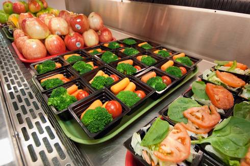 Cafeteria trays full of fresh fruits and vegetables.