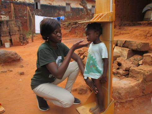 Mary Adjepong measures a child in Ghana