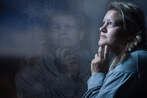 Woman looking out glass window as it rains.