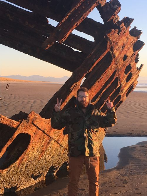 Huron Pines AmeriCorps member Adam Ziani stands near a shipwreck on the Pacific Coast. He hopes to translate his Pacific Coast experiences to help inspire Great Lakes explorations among youth in Northeast Michigan.