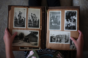 Person holding old photo book with grayscale pictures.