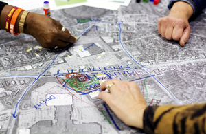 Photo of the hands of three people working together during a charrette on making design changes to a aerial map of a community.