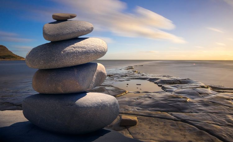 Rocks stacked neatly on a beach.