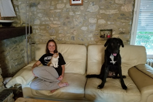 Emily with a cat and dog on a couch.
