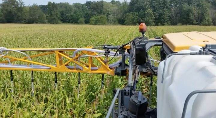 Using a converted sprayer to broadcast seed cover crops between corn.