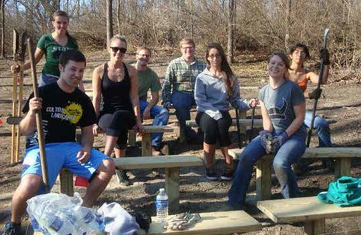 Photo of landscape architecture students taking a break while volunteering at Woldumar Nature Center.