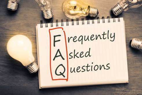 FAQ on notepad with light bulbs in the background