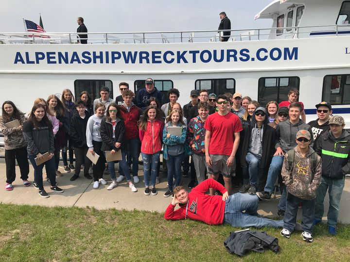 A large group of high school students stand on shore in front of a glass-bottom boat they were going to ride on to explore Lake Huron heritage and habitats as part of their Science in the Sanctuary class. On the boat in the background are the words alpenashipwrecktours.com. Photo: Michelle Cornish, Alpena High School