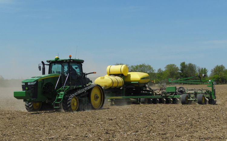 A planter planting soybeans in a field.